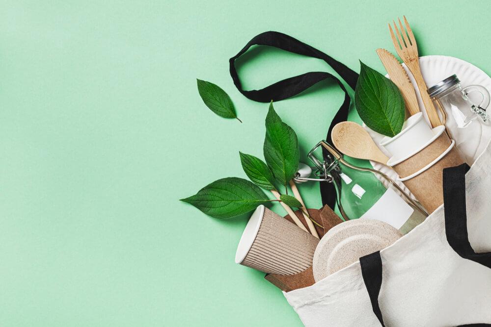 Różne ekologiczne opakowania i drewniane sztućce wysypujące się z bawełnianej torby. Zielone tło.