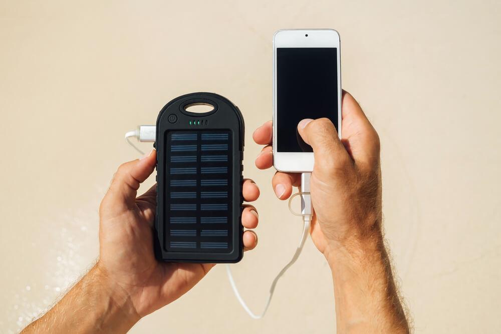 telefon ładowany powerbankiem zasilanym światłem słonecznym.